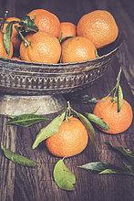 Zinkschale mit Mandarinen auf dunklem Holz