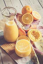 Orangen, Karaffe und Glas frisch gepresster Orangensaft auf Tuch und Holz