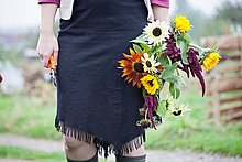 Waist down view of woman cutting fresh flowers at allotment