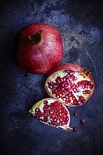 Geschnittener und ganzer Granatapfel auf dunklem Grund