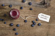 Blueberry Smoothie in Flasche, Schild und Blaubeeren auf Holz