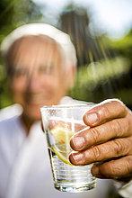 Nahaufnahme eines älteren Mannes, der ein Glas Wasser hält.