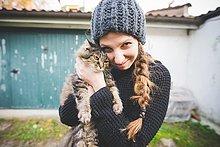 Junge Frau mit Strickmütze kuschelnde Katze, Blick auf die Kamera lächelnd