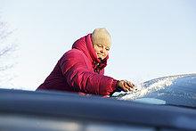 Schweden, Sodermanland, Mittlere erwachsene Frau, die Schnee von der Windschutzscheibe kratzt