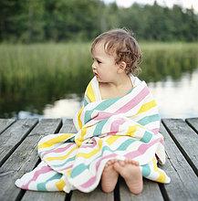 Finnland, Uusimaa, Lapinjarvi, Porträt eines Mädchens (2-3) in Handtuch gewickelt am Steg sitzend