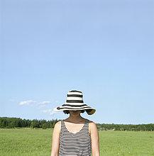 Finnland, Uusimaa, Lapinjarvi, Frau mit Hut im Gesicht