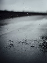 Regentropfen spritzen auf Asphalt