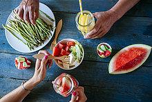 Nahaufnahme der Hände beim Essen von Salat, Wassermelone, Limonade, Spargel und Süßigkeiten