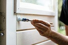 Mann malt innerhalb einer Tür weiß