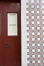 Rote Tür und verzierte Fliesenwand