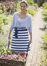 Portrait lächelnder Pflanzenzüchter beim Schubkarrenschieben im sonnigen Garten