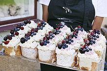 Bäckerin mit Backblech außerhalb des Cafés