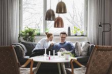 Paar, das im Smartphone schaut, während es zu Hause auf dem Sofa sitzt.