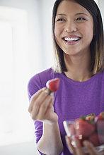 Glückliche junge Frau schaut weg, während sie eine Schale mit Erdbeeren hält.