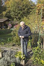 Full length portrait of happy senior man working in vegetable garden