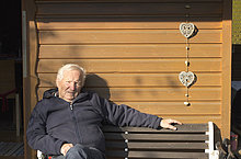 Portrait of contented senior man sitting on bench against garden shed
