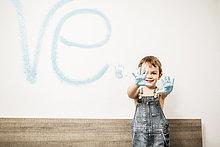 Porträt eines lächelnden kleinen Jungen, der seine Handflächen voller hellblauer Farbe zeigt.