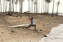 Indonesien, Bali, Frau mit Surfbrett am Strand