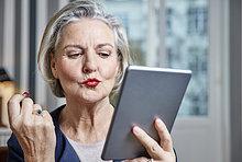 Seniorenfrau mit Lippenstifttablette