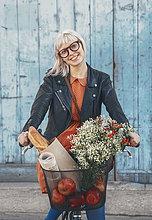 Lächelnde junge Frau mit Lebensmitteln auf dem Fahrrad