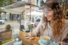 Lächelnde junge Frau in einem Cafe schaut auf ihr Handy