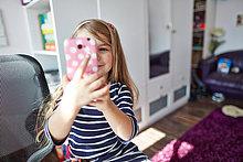 Lächelndes Mädchen hält ein Handy