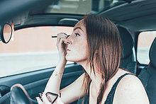 Junge Frau mit Sommersprossen mit Lidschatten im Autospiegel