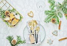 Weihnachtlich gedeckter Tisch mit Goldbesteck und Plätzchen