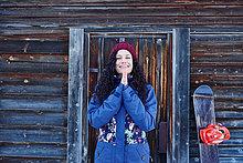 Porträt der Frau in Strick Hut üben Yoga, mit den Händen zusammen durch Blockhaus
