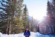 Frau übt Yoga, meditiert in schneebedeckten sonnigen Wald, Österreich