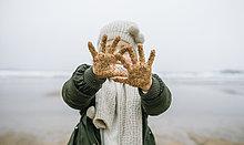 Mädchen zeigt ihre sandigen Hände am Strand im Winter