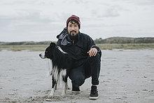 Niederlande, Schiermonnikoog, Mann mit Border Collie am Strand