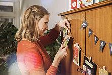 Frau beim Aufhängen Weihnachtskarten zur Dekoration