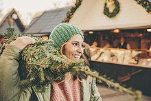 Glückliche Frau mit einem eingewickelten Baum, die über den Weihnachtsmarkt läuft.
