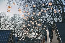 Dekoration von Papiersternen auf Bäumen über den Dächern des Weihnachtsmarktes in der Abenddämmerung