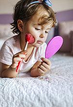 Porträt eines kleinen Mädchens auf dem Bett liegend mit Handspiegel und Kosmetikpinsel