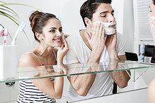 Junges Paar am Morgen vor dem Spiegel