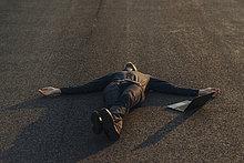 Geschäftsmann auf einer Straße neben dem Laptop liegend