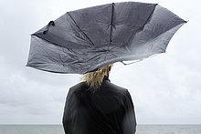 Polen, Niechorze, Frau unter schwarzem Regenschirm beim Beobachten der Ostsee