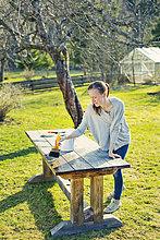 Finnland, Paijat-Hame, Heinola, Mittlere erwachsene Frau ölt Holztisch im Garten