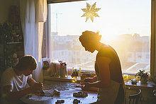 Finnland, Helsinki, Paar beim Zubereiten von Weihnachtsgebäck