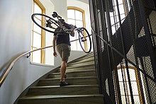 Schweden, Radfahrer mit Fahrrad auf der Treppe