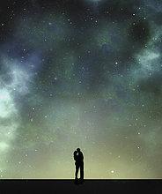 Silhouette eines küssenden Paares vor Sternenhimmel