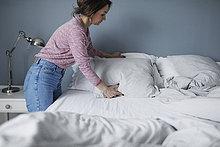 Seitenansicht der Frau, die die Kissen auf dem Bett zu Hause anordnet.