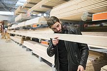 Männlicher Kunde untersucht Holzbohle im Baumarkt