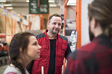 Lächelnder Verkäufer beim Anblick eines Paares im Baumarkt