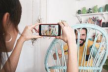 Junge Frau fotografiert den bärtigen Mann, der zu Hause einen Korbsessel malt.