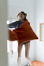 Verspielte junge Frau mit Kissen im Schlafzimmer
