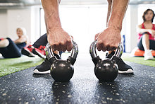 Nahaufnahme des Mannes beim Training mit Kettlebells im Fitnessstudio