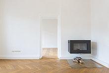 Geräumiges leeres Wohnzimmer mit Fischgrätparkett und Kamin